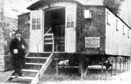 """Le pasteur Scarabin devant la """"semeuse"""" ou """"déménageuse"""" à Guingamp en 1925, quartier Sainte-Croix. Cette salle mobile sur roues avait été construite pour le pasteur Émile Ullern en Savoie puis achetée par la mission méthodiste. La Mission populaire Évangélique fournissait le camion pour la tracter. Elle pouvait accueillir jusqu'à 80 personnes."""